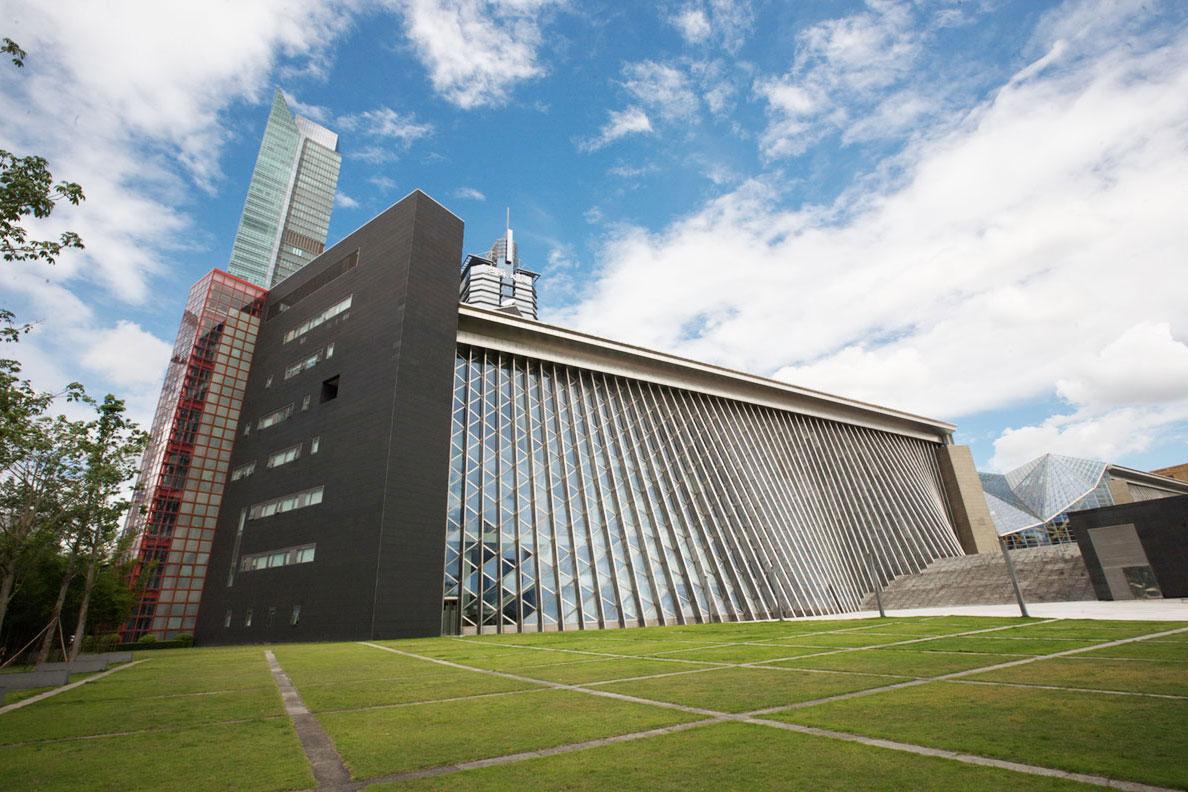 """新馆建筑由世界著名的日本建筑师矶崎新先生主持设计,和音乐厅一道构成深圳文化中心。寓意文化森林的图书馆正门""""银树""""和音乐厅正门""""黄金树""""象征中心区文化城的""""城门""""。图书馆南侧的三栋黑色放射性建筑状若三本翻开的图书,而东面柔美变化的水幕和三维玻璃曲面犹如委婉韵律的竖琴,从莲花山鸟瞰,阳光下熠熠生辉,可谓刚柔并济,煌煌大观。"""